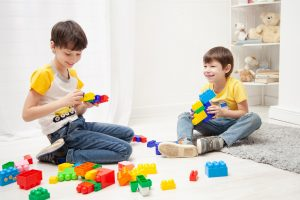 Two young brothers playing happily with Duplo bricks, smiling at each other not feeling anxious.